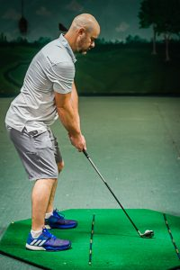 Golfer using alignment sticks for proper golf alignment at Howard's Golf indoor driving range