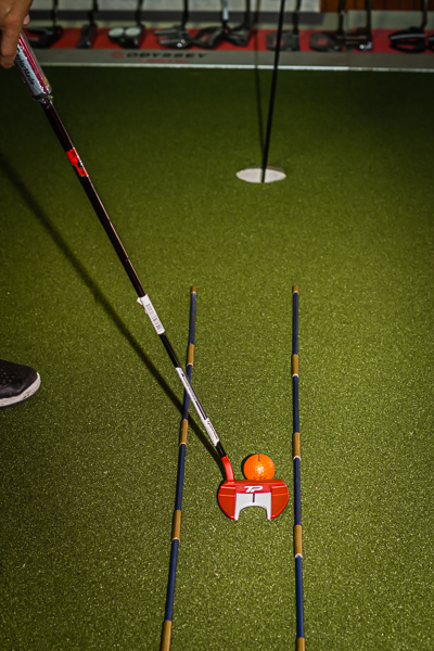 Putting drills like this here have a TaylorMade Putter aligned with Titleist alignment sticks with Odyssey putters in the background at Howard's Golf