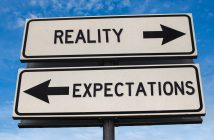 Picture of road signs pointing opposite ways saying Reality and Expectations